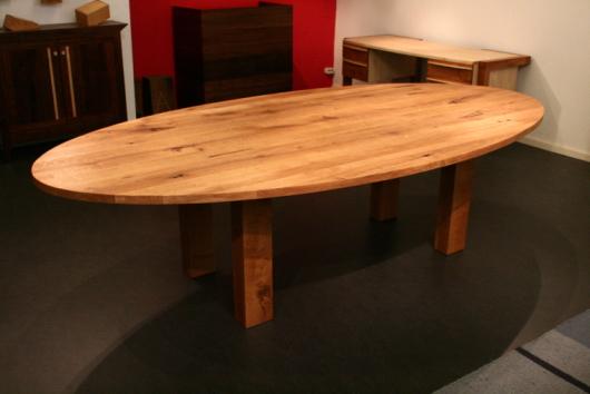 Een ellipsvormige eikenhouten tafel